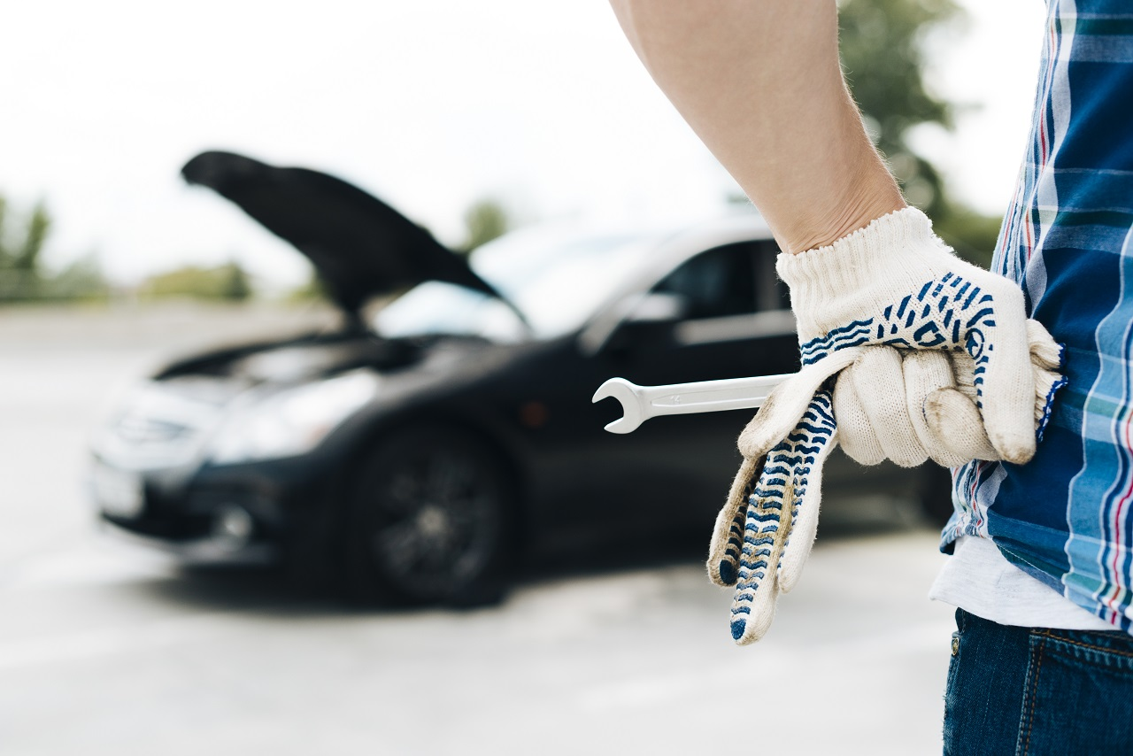 Hands holding gloves and a wrench in the foreground with a car with its hood popped up is in the background