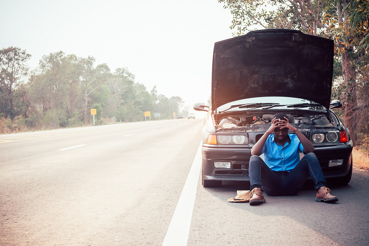 A man sitting in front of his broken down car on the side of the road