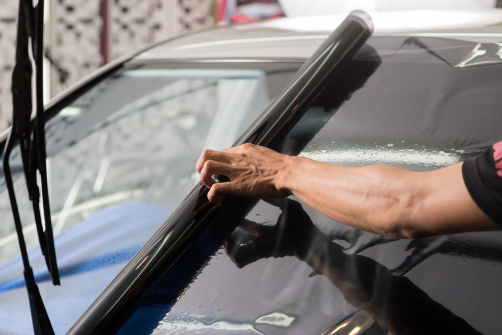 Car window tint being placed on windshield