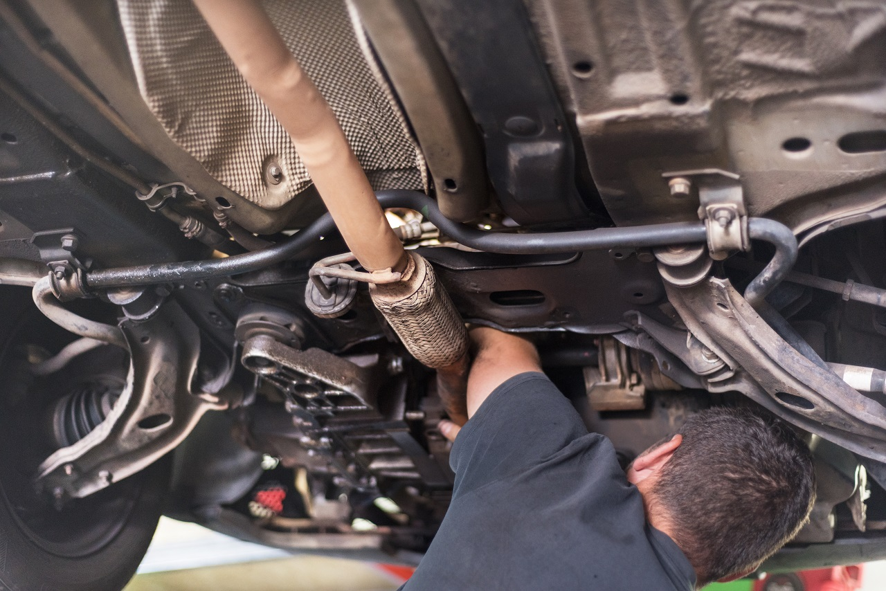 A mechanic repairing a hanging exhaust