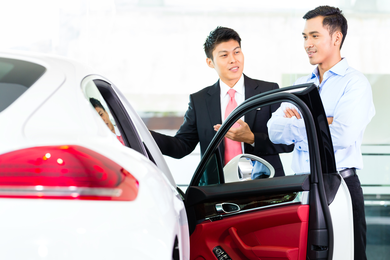 A car salesman showing a new car to a customer