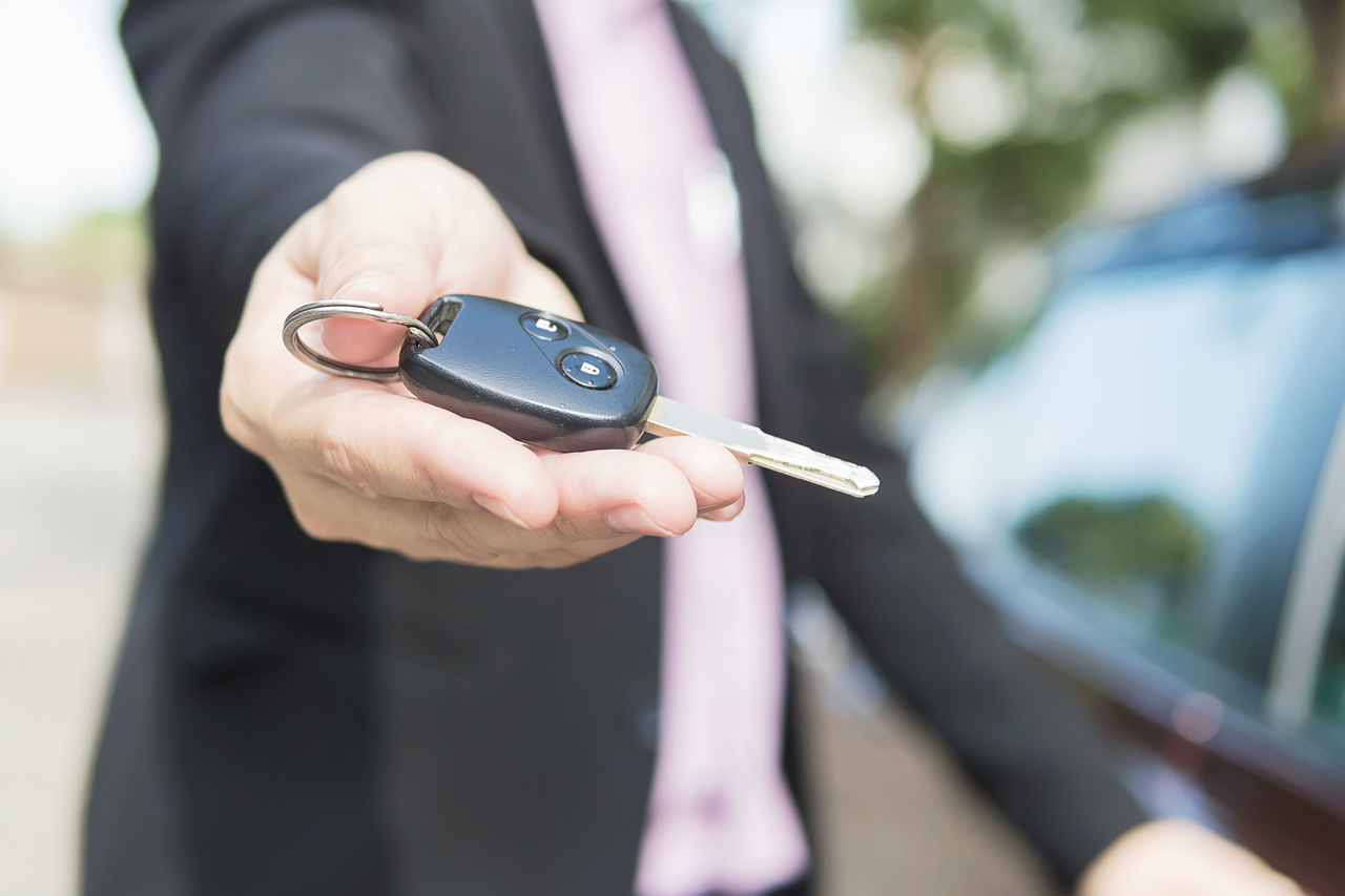 A man showing off the keys of his newly purchased car