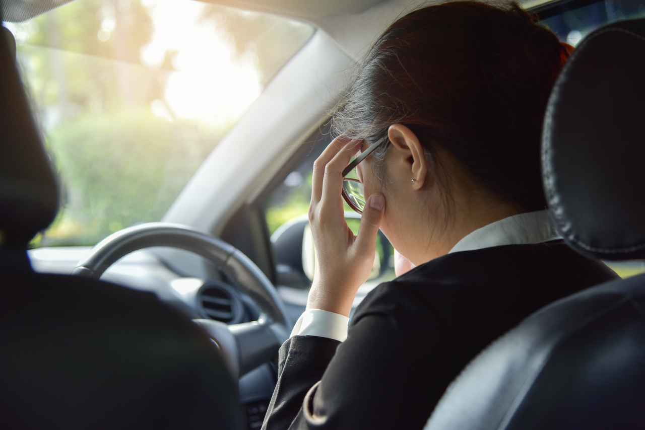 A businesswoman stressed in a car