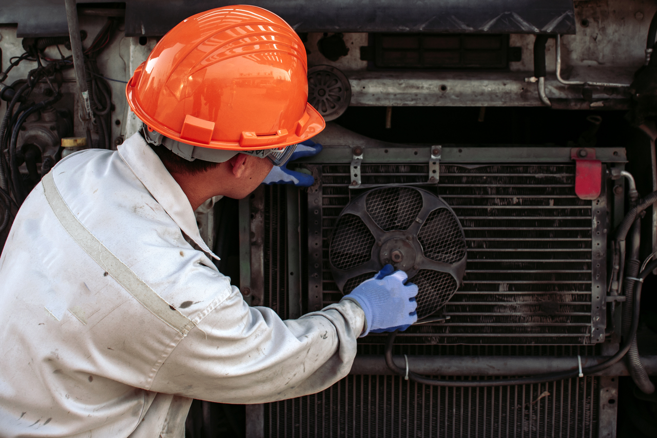 A mechanic inspecting a broken cooling fan