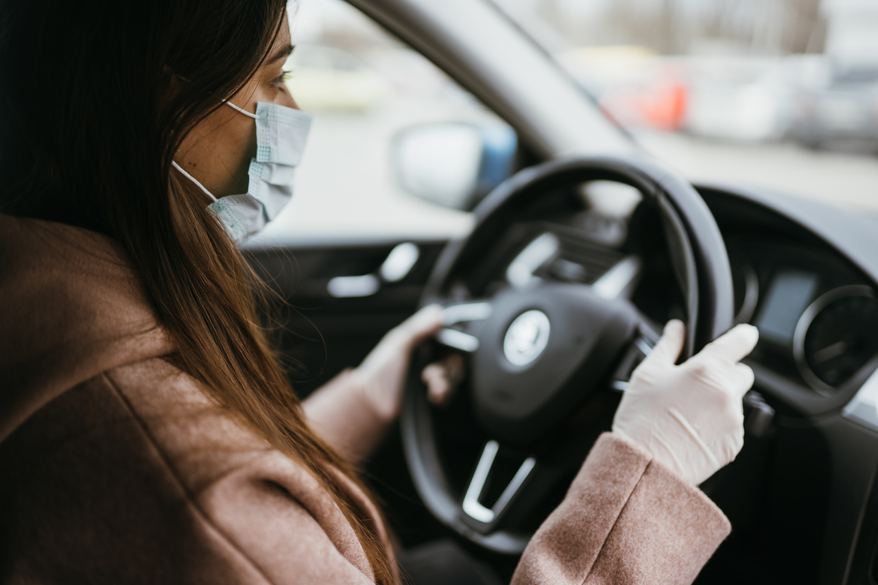 A woman in a mask driving during the pandemic