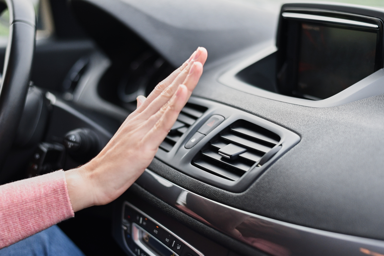 A driver's hand feeling hot air from the aircon
