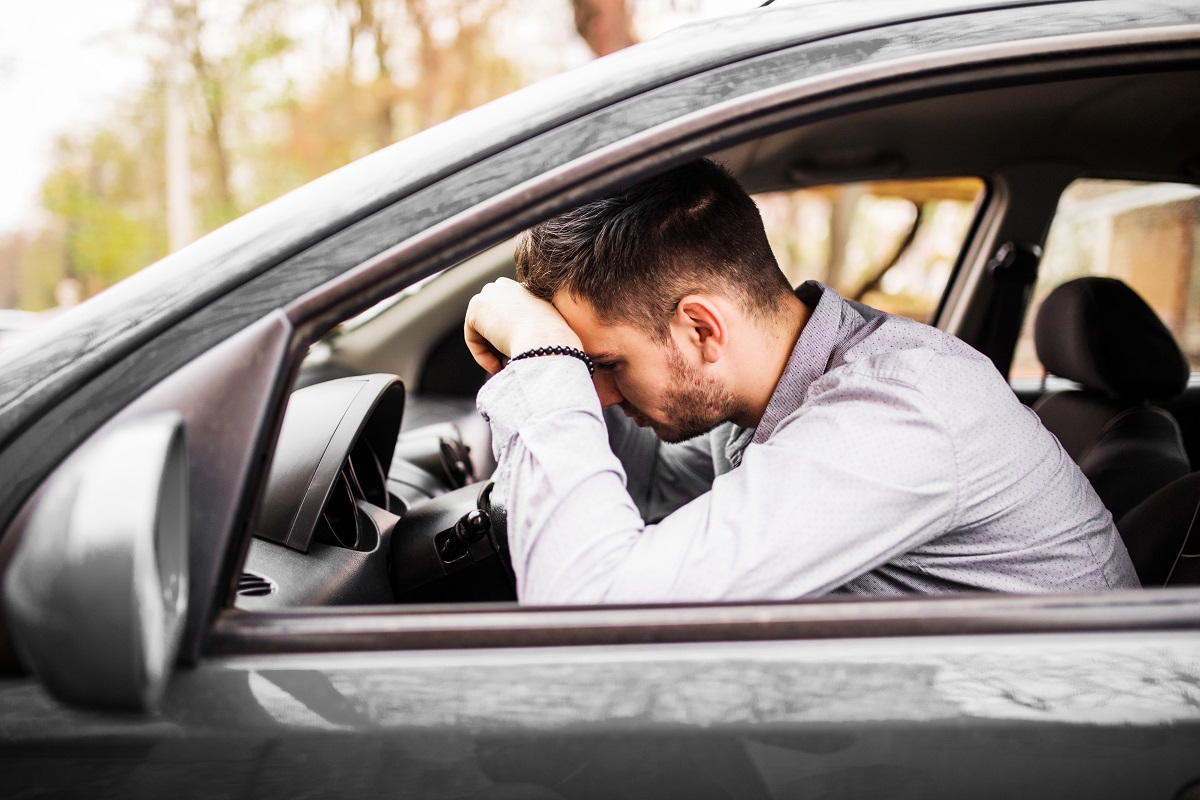 Young man sitting in car very upset and stressed after hard fail