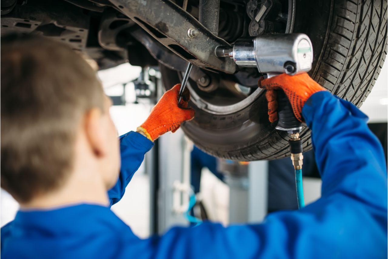 Car mechanic installing a suspension