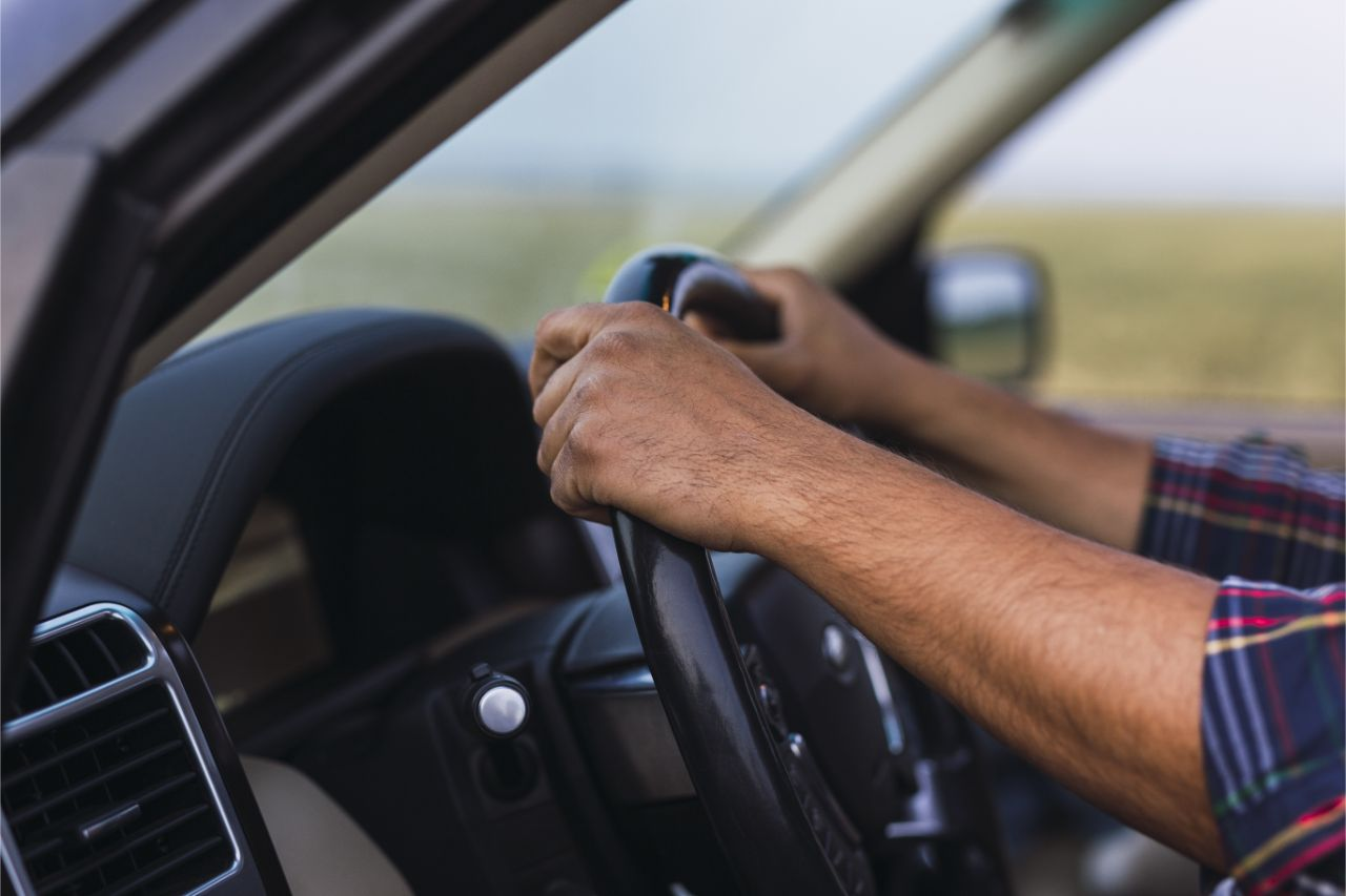 Close up of hands on a steering wheel