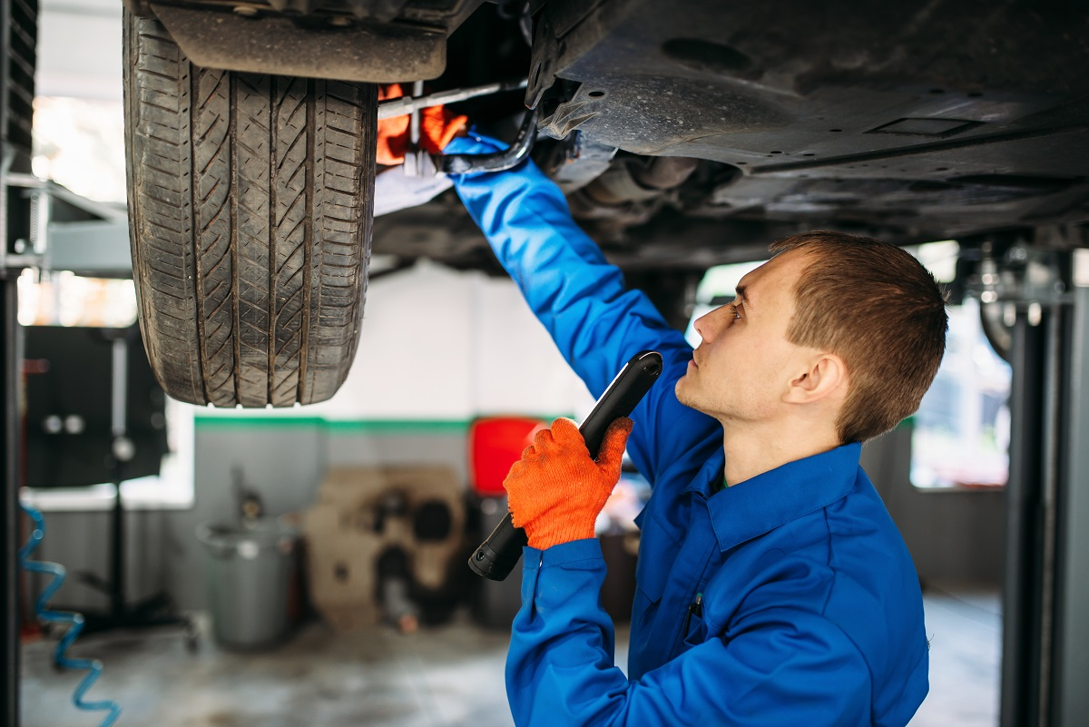 Mechanic with lamp checks the car suspension