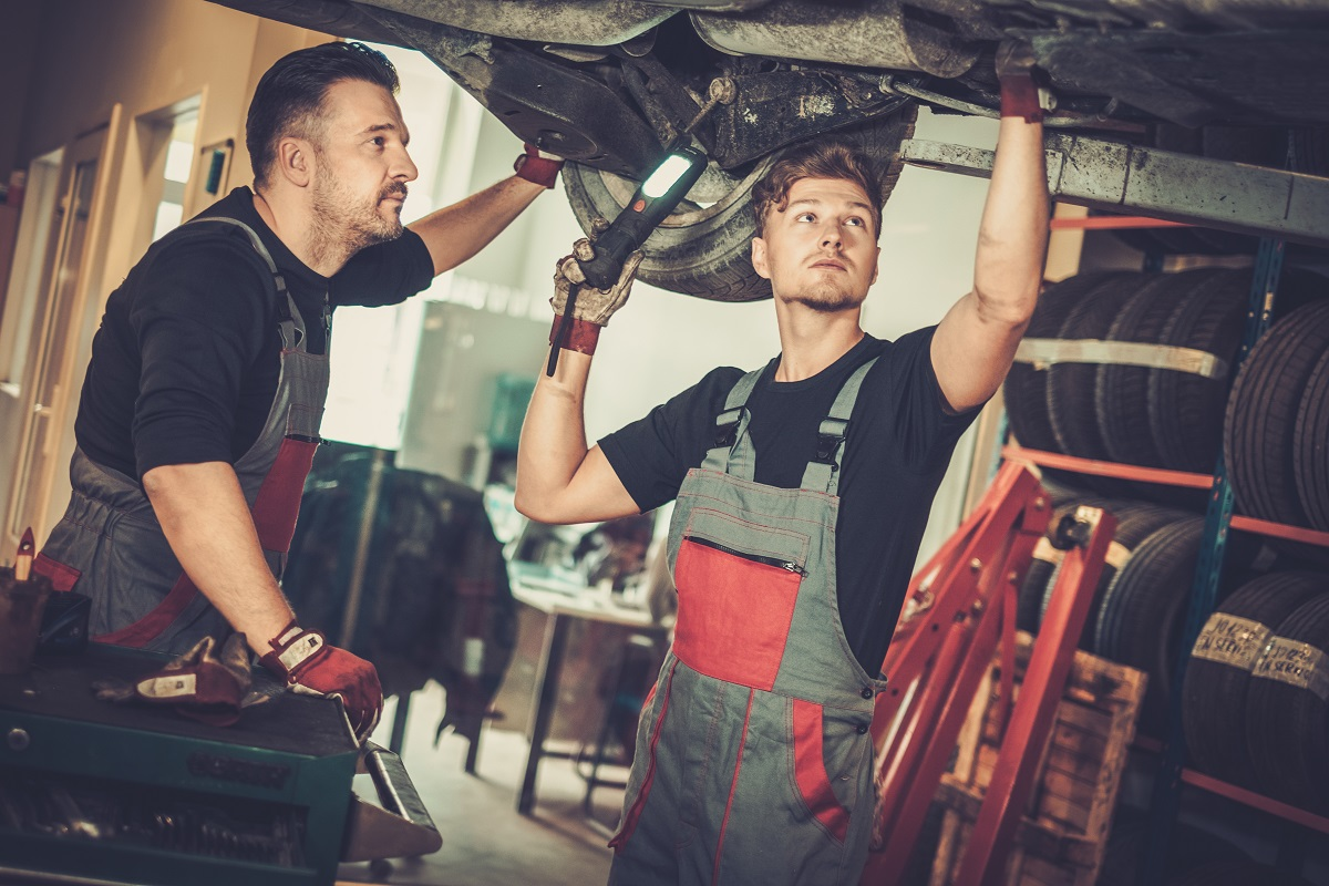 Professional car  mechanics  working under lifted car in auto re